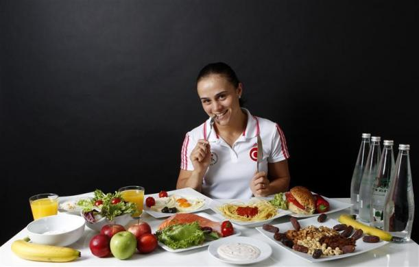 Turkish wrestler and Olympic hopeful Elif Jale Yesilirmak poses in front of her daily meal intake in Ankara