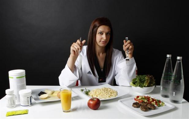 Turkish Taekwondo fighter and Olympic hopeful Nur Tatar poses in front of her daily food intake in Ankara